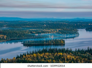 A hazy island in summit lake covered in fall colors. Shot at dusk from the top of Teapot mountain - Prince George - British Columbia - Canada