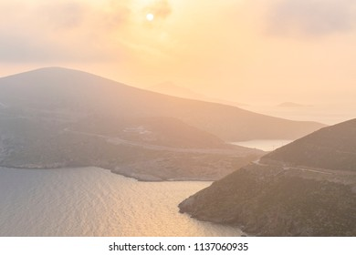 Hazy morning view of Fourni coastline and Agios Minas island in the distance, Greece.