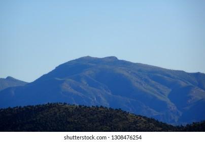 A hazy mountain backdrop beneath a pale blue sky; Tonto National Forest in Arizona