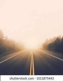 A hazy mountain road covered in fog goes straight into the distance. Low hanging clouds hide the horizon