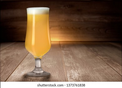Hazy NEIPA New England IPA pale ale craft beer, on wood surface, rich frothy foam head with copy space