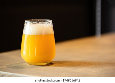 Hazy NEIPA New England IPA pale ale beer, on wood surface, rich frothy foam head with copy space