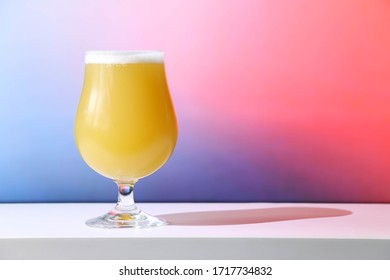 A hazy New England India pale ale beer in a tulip shaped glass against a soft background.