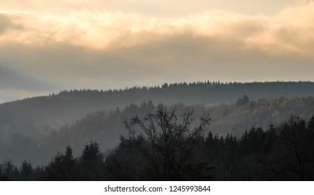 Hazy pastel orange sunset with hazy trees on hills