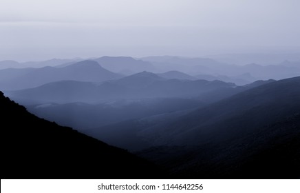 Hazy silhouetted mountains in blue tones in the Colorado Rocky mountains
