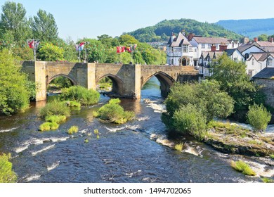 Hazy summer afternoon in Llangollen, Wales. River Dee flows quickly under an old arched bridge