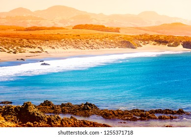 Hazy summer afternoon overlooking rocky shoreline and bright blue ocean with waves breaking onto sandy beach under an orange smoggy sky.