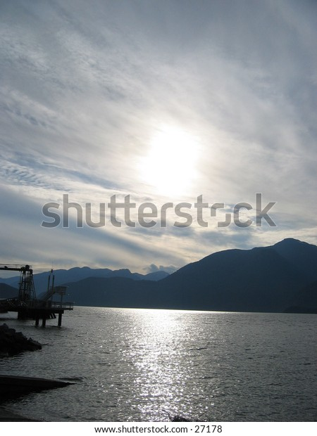 A hazy sunset behind clouds from the shore in Squamish BC, Canada