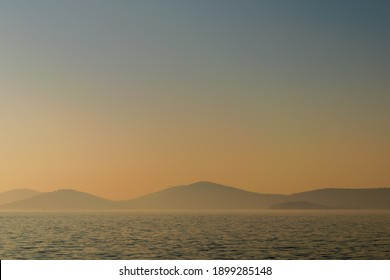 Hazy sunset seascape with sea horizon and clear sky, with mountain islands in the far end, Princes Islands, Sea of Marmara near Istanbul, natural photo background