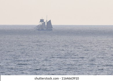 A hazy tall masted ship in the distance