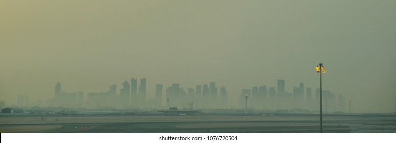 A hazy view of the city of Doha in Qatar, Middle East. The skyline of skyscrapers is faintly visible.