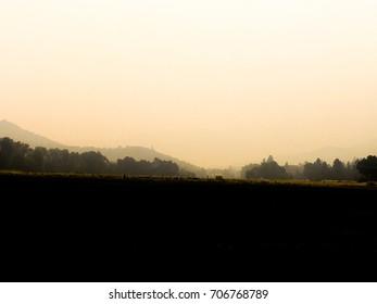 Hazy view of ranch on horizon.