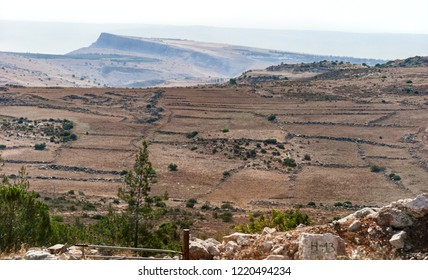hazy vista of Mt Arbel in the lower galilee with stone fenced fields in the foreground and the golan heights in the background