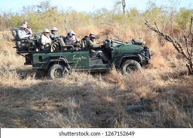 HAZYVIEW, SOUTH AFRICA - SEPTEMBER 30, 2018: Tourists in safari vehicle observing African leopard in Sabi Sands Game Reserve, South Africa