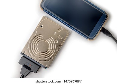 hdd 2.5 hard drive disk connected to smartphone via sata usb cable closeup overhead view