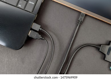 hdd 2.5 internal hard drive disk connected to laptop and digital table via sata usb cable closeup view
