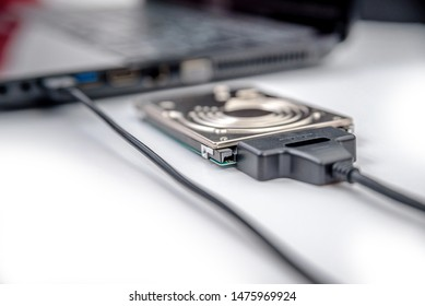 hdd 2.5 internal hard drive disk connected to laptop via sata usb cable closeup view