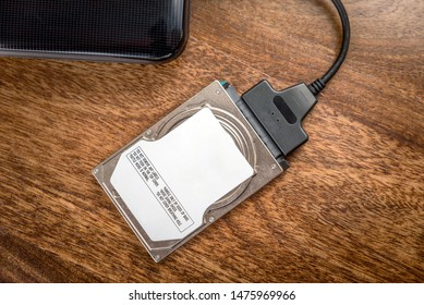 hdd 2.5 internal hard drive disk connected to laptop via sata usb cable on wooden table closeup view