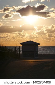 HDR image of a lifeguard station on Miami Beach, Florida silhouetted against the setting sun with an orange sky