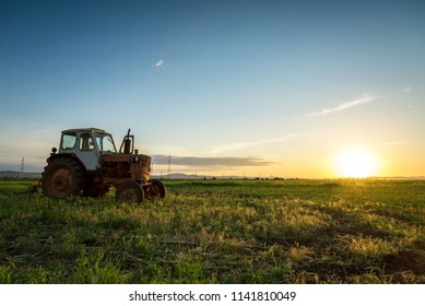 HDR image of old rusty tractor in a field. Sunset shot.