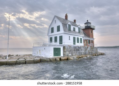 HDR image of Rockland Harbor Breakwater Lighthouse at high tide under cloudy sky with rays of sunlight shining down on ocean in Maine