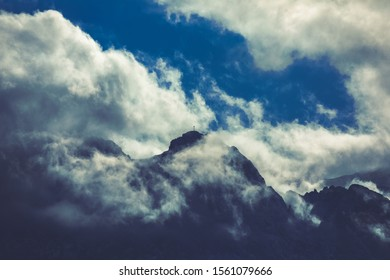 HDR photo of the Tatra Mountains and Great Giewont Peak with the steel Cross between clouds.