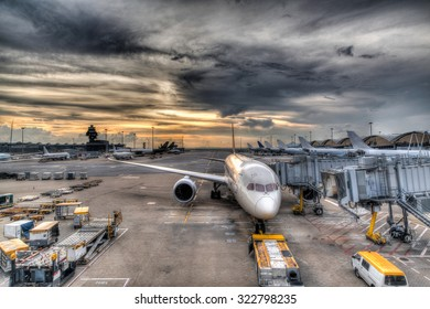 HDR rendering of a golden sunset over Hong Kong International Airport while a plane awaits refueling and servicing before resuming its flight.