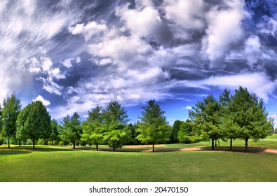 HDRI panorama of a park in summer with a dramatic sky.