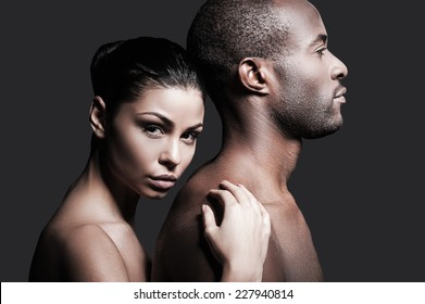 He is absolutely mine. Beautiful Caucasian woman bonding to back of handsome African man and looking at camera while both standing against grey background