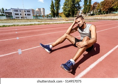 He aimed for victory. Portrait of a handsome male athlete looking depressed after his loss in the competition sitting on the racetrack alone copyspace