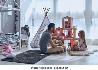 He always understands her. Father and daughter playing with a dollhouse together while sitting on the floor in bedroom