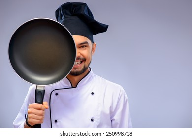 He is a best chef ever. Closeup portrait of handsome cook covering a half of his face with a frying pan and smiling while standing against grey background with copy space