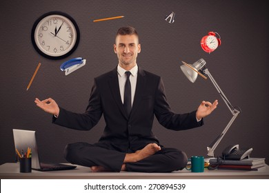 He is businessman that can relax in office, while his work is doing. Handsome businessman sit on table in office in lotus position and try to relax.