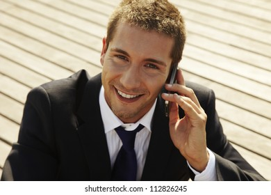 he is calling somebody by mobile telephone on the street