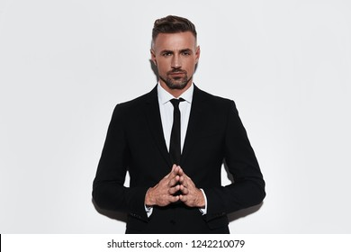 He got great style. Handsome young man in full suit keeping hands clasped and looking at camera while standing against white background