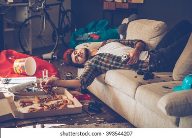 He had too much beer. Young handsome man passed out on sofa with pizza slice and beer can in his hand in messy room after party