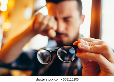 He has eyesight problems. guy with beard is holding his eyeglasses right in front of camera with one hand and rubbing his eyes with another hand. Focus is on eyeglasses