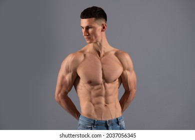 He has a spectacular torso. Shirtless guy with muscular torso. Fit man grey background