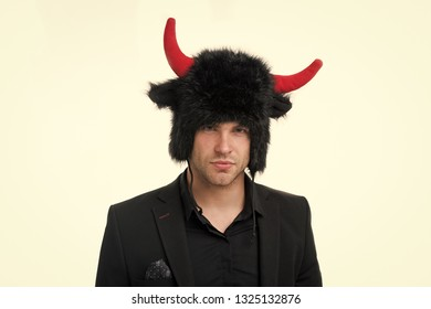 He has stubborn character. Man strict face wears hat of devil or bull with horns. Guy black classic suit strong character or temper. Businessman needs to be confident stubborn and strong in behavior.