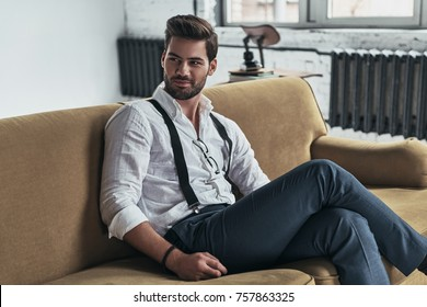 He knows all of your secrets. Handsome young man in white shirt and suspenders looking away and smiling while sitting on sofa