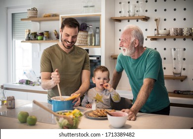 He learned from his dad to cook. Grandfather his adult son and grandson together in kitchen. lunch
