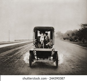HE LETS HER STEER WHILE HE GETS HER EAR. Affectionate young couple enjoying the privacy of an automobile in 1907