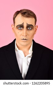 He is much of an actor. Mime with face paint. Mime artist. Man with mime makeup. Theatre actor miming. Stage actor miming. Theatrical performance art and pantomime. Comedian or tragedian performer.