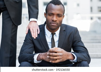 He needs a friendly support. Frustrated young African man in formal wear sitting on staircase while someone touching his shoulder with hand