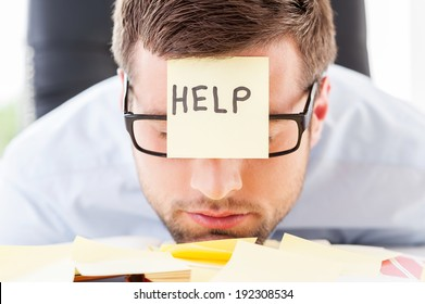 He needs help. Frustrated young man in formal wear with adhesive note on his forehead leaning his head at the table