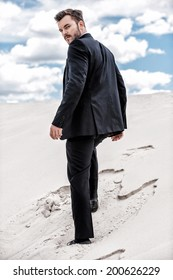He is on his way to success. Rear view of young man in formalwear rising up by desert dune