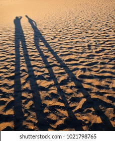 He and she. Shadows on the beach.