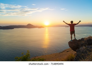 He stood looking at the sunrise on the rock. Along with open arms to get Vitamin D.
