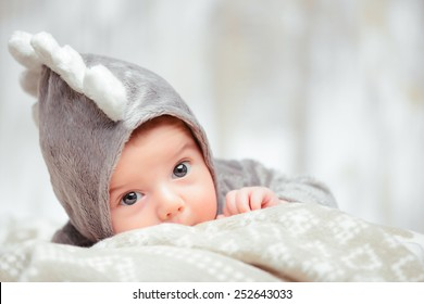 He is such a funny little guy. Closeup of a cute little baby in dinosaur bodysuit lying on the blanket