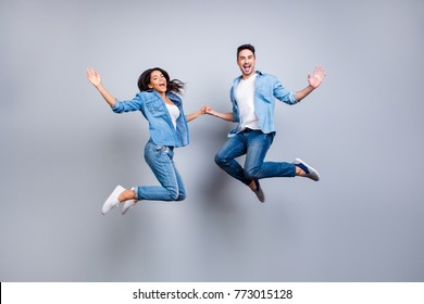 He vs She full length portrait of attractive, playful, cheerful, hispanic couple in casual outfit jumping with opened mouths over grey background